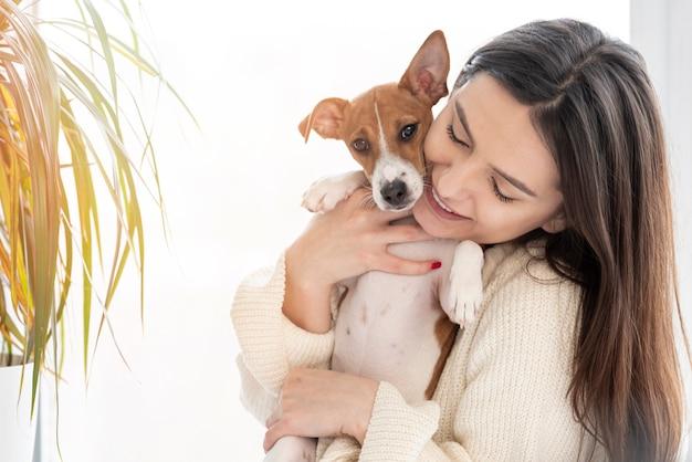 Mujer posando mientras sostiene a su perro con planta