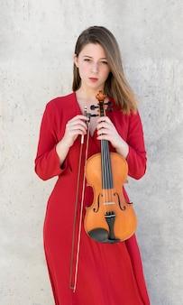 Mujer posando mientras sostiene el violín y el arco
