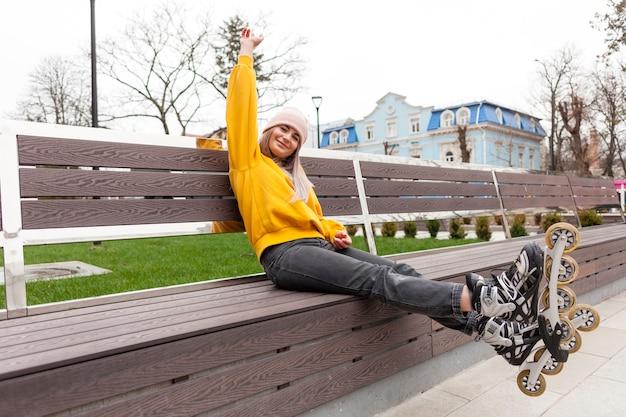 Mujer posando mientras usa patines y gorro