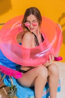 Mujer posando con salvavidas rosa