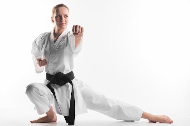 Mujer en pose de karate tiro completo