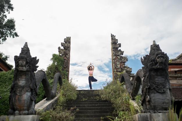 Mujer en pose de yoge en escaleras de piedra antigua entrada del templo puerta balinesse
