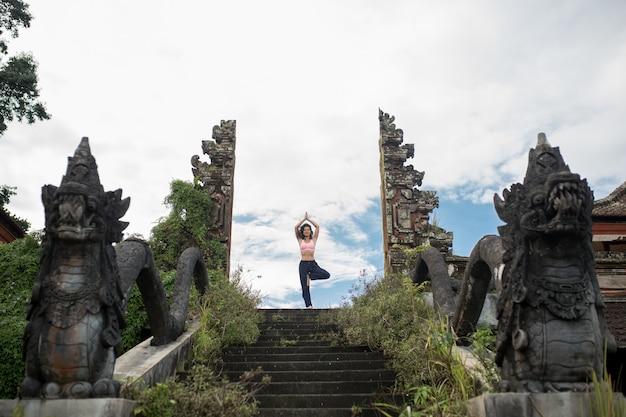 Mujer en pose de yoge en escaleras de piedra antigua entrada del templo puerta balinesse.