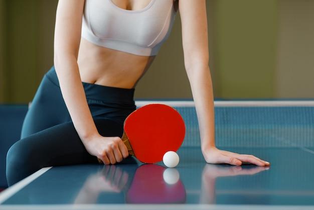 Mujer con poses de raqueta en la mesa de ping pong