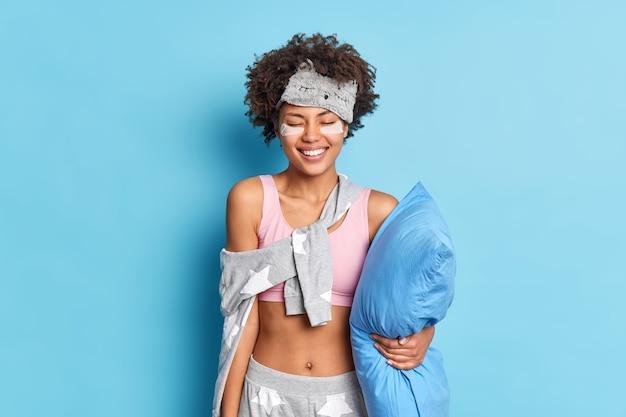 Mujer positiva con cabello rizado se despierta por la mañana entusiasmada satisfecha después de tener buenas poses de sueño nocturno en pijama sostiene almohada aislada sobre pared azul