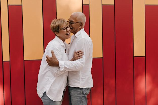 Mujer positiva con cabello rubio en camisa blanca y anteojos riendo y abrazándose con hombre de pelo gris en rojo y naranja.