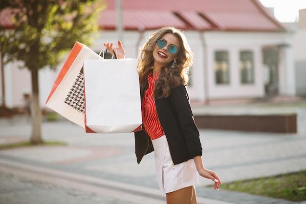 Mujer positiva caminando en la calle después de ir de compras con muchas bolsas de papel.