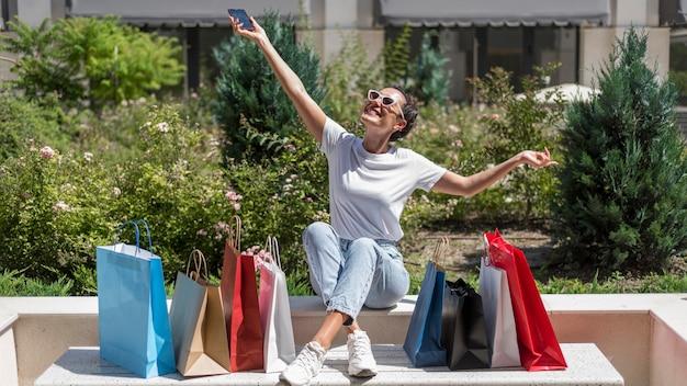 Mujer positiva celebrando bolsas de la compra.
