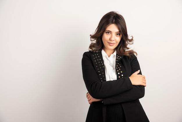 Mujer positiva en chaqueta negra posando en blanco