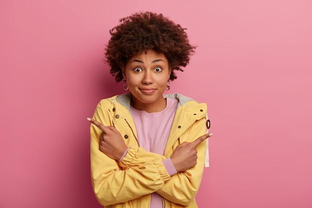 Mujer positiva confundida con cabello afro apunta ambos dedos índices en lados diferentes, demuestra dos direcciones, muestra algo a la izquierda y a la derecha