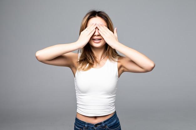Mujer positiva emotiva que cubre los ojos con las manos y sonríe ampliamente, intrigada mientras espera sorpresa sobre la pared gris.