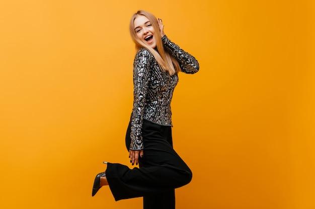 Mujer positiva extática en zapatos de tacón de pie en la pierna ine. mujer alegre en pantalón negro bailando en naranja