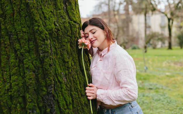Mujer positiva con la flor cerca del árbol en el parque