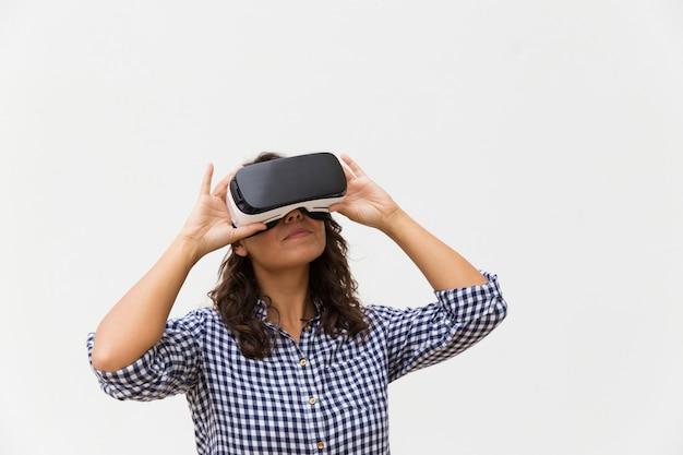 Mujer positiva con gafas de realidad virtual, disfrutando de la experiencia