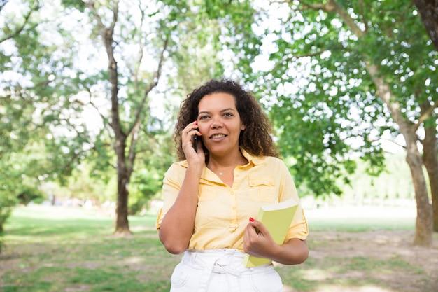 Mujer positiva hablando por teléfono y sosteniendo el libro en el parque de la ciudad