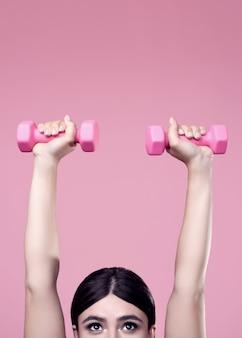 Mujer positiva haciendo ejercicio con pesas