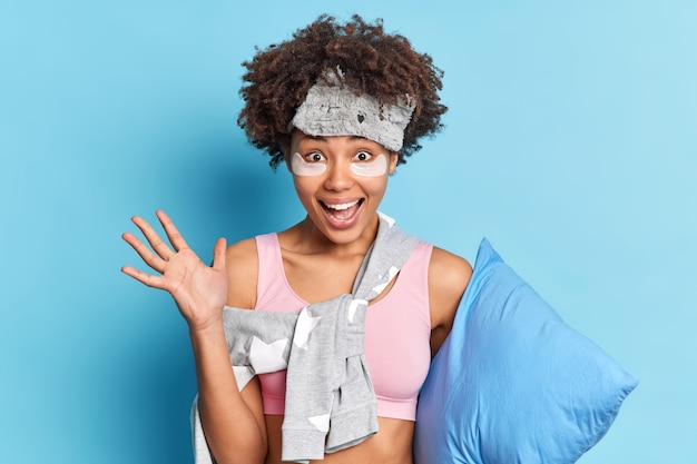 Mujer positiva levanta la palma contenta de descansar después de una dura semana disfruta de la pereza y la relajación mantiene la palma levantada sostiene la almohada aislada sobre la pared azul emocionada con buenos sueños