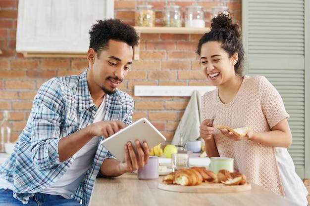 Mujer positiva o ama de casa mira con una sonrisa mientras hace sándwiches, mira videos divertidos