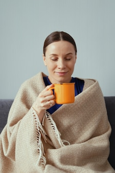 Mujer positiva que goza de una taza de té envuelta en una manta