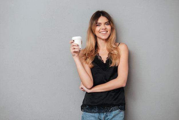 Mujer positiva que sostiene la taza de café