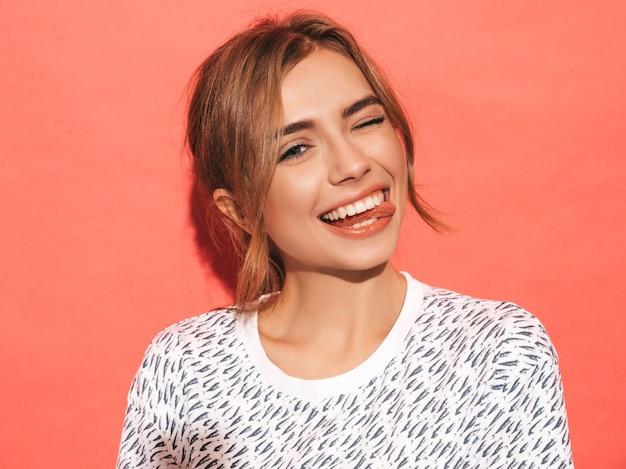 Mujer positiva sonriendo. modelo divertido posando junto a la pared rosa en el estudio. muestra lengua y guiños