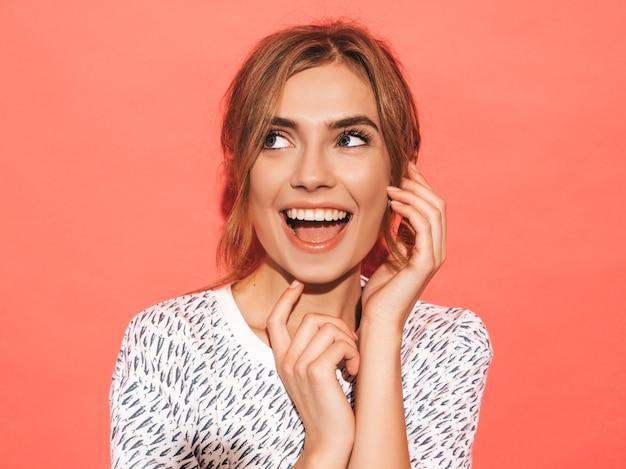 Mujer positiva sonriendo. modelo divertido que presenta cerca de la pared rosada en estudio