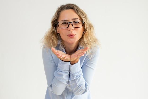 Mujer positiva en vasos frunciendo los labios y soplando beso de aire