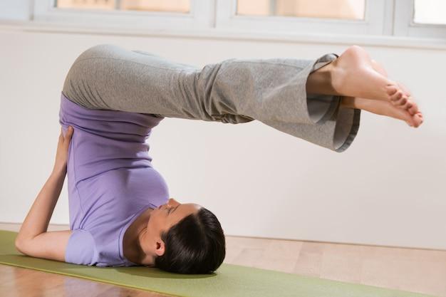 Mujer en una postura de yoga estiramiento tradicional en casa o gimnasio