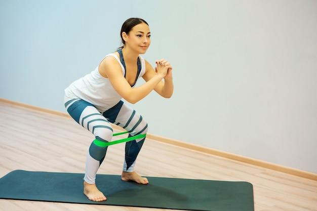 Una mujer practica deportes con una banda elástica se pone en cuclillas en casa