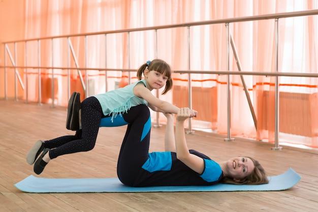 La mujer practica deportes levantando las piernas de una niña.