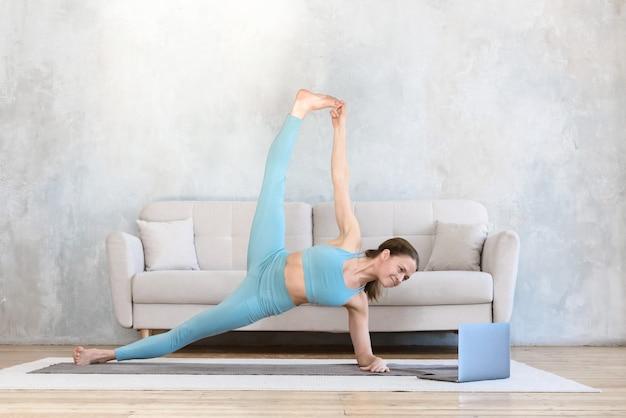La mujer practica deportes en línea usando la computadora portátil desde casa practicando yoga y estiramientos