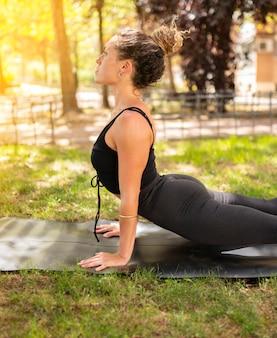 Mujer practica pose de yoga al aire libre