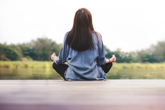 La mujer practica yoga al aire libre. sentado en posición de loto.