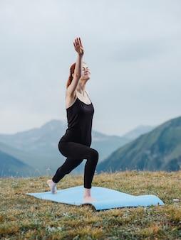 Mujer practica yoga en una alfombra al aire libre en las montañas turismo aire fresco