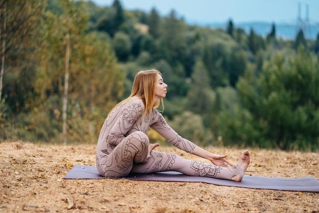 Una mujer practica yoga en la mañana en un parque al aire libre.