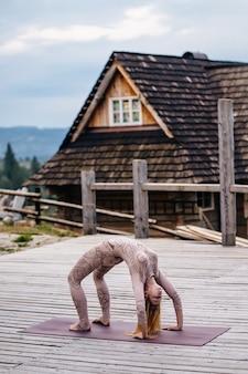 Una mujer practica yoga por la mañana en una terraza al aire libre.