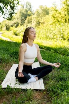 Mujer practica yoga y medita en posición de loto en la playa