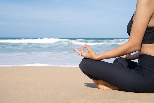 La mujer practica yoga y medita en la posición de loto en la playa