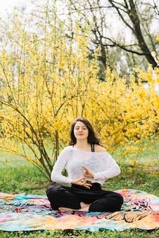 Mujer practicando meditación con gesto de gyan mudra en la naturaleza