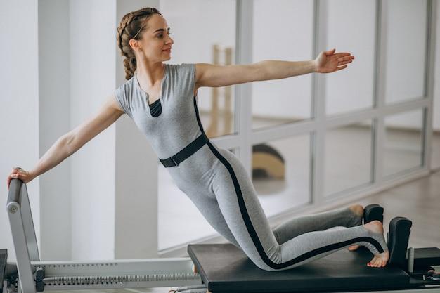 Mujer practicando pilates en un reformador de pilates