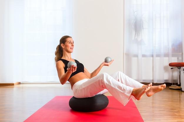 Mujer practicando poses en pelota de ejercicio