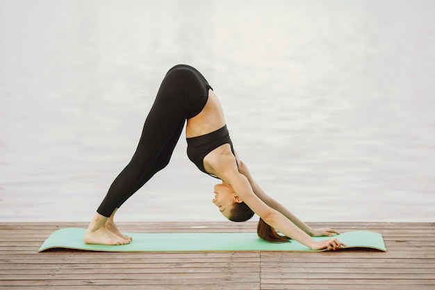 Mujer practicando yoga avanzado por el agua