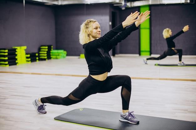 Mujer practicando yoga en la colchoneta en el gimnasio