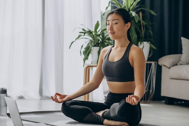Mujer practicando yoga en estera en casa
