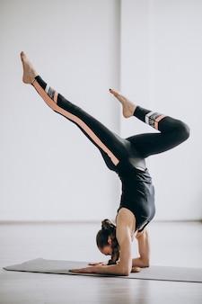Mujer practicando yoga en una estera
