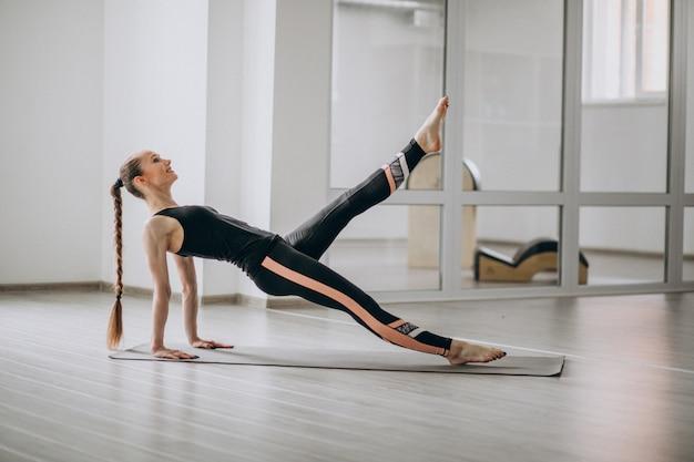 Mujer practicando yoga en el gimnasio sobre una estera