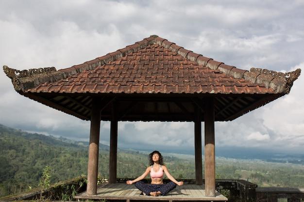 Mujer practicando yoga en la glorieta tradicional balinesa