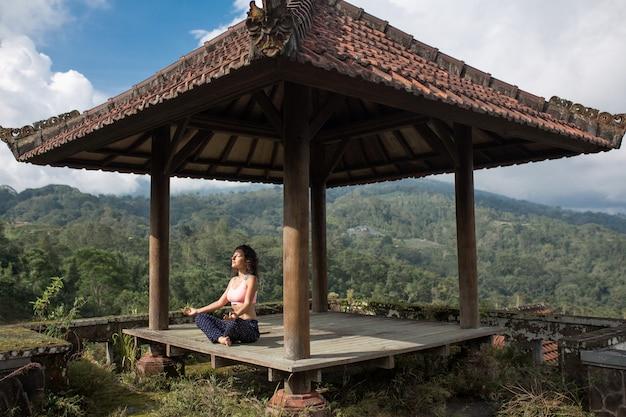Mujer practicando yoga en la glorieta tradicional balinesa.