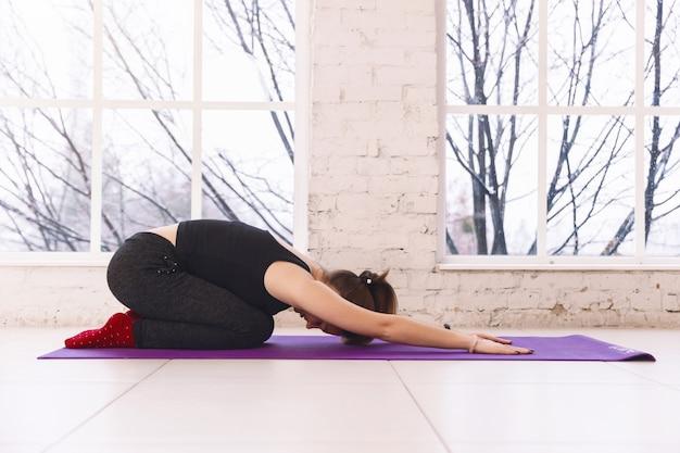 Mujer practicando yoga, haciendo una pose infantil balasana en el piso de la sala de luz sobre una colchoneta de yoga