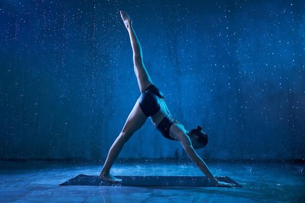 Mujer practicando yoga bajo la lluvia